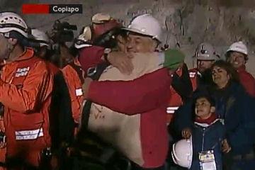 1人目: Florencio Ávalosさん(手前)とピニェラ大統領が抱き合う。右に7歳の息子バイロン君と妻モニカさん