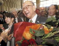 北大での受賞記念セレモニーに出席し、花束を手に報道陣の取材に答える鈴木章・北大名誉教授