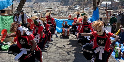 Japanese performers dance at a temple in the tsunami-devastated area of Rikuzentakata, Japan, on April 17